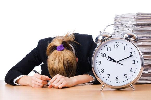 tired woman desk deadline paper work clock alarm