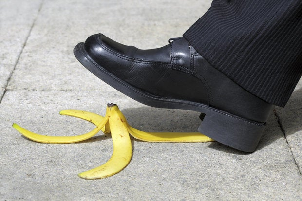 businessman foot stepping on banana peel