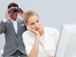 Manager using binoculars to see colleague's computer screen 125728197
