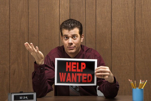 Caucasian mid-adult retro businessman sitting at desk holding help wanted sign with pleadin126468756
