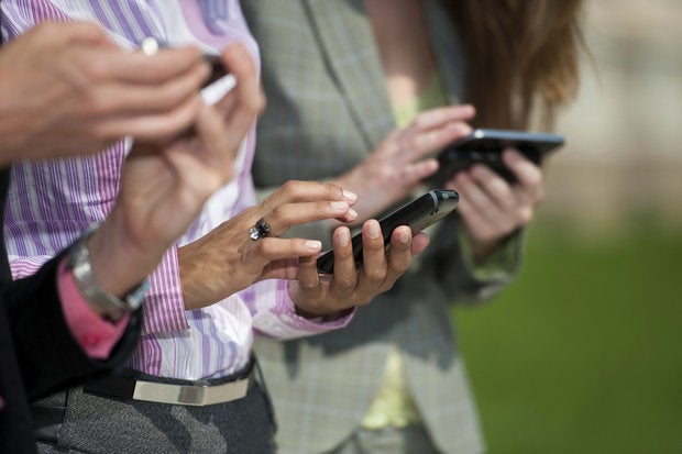 Three business users with mobile devices smartphones