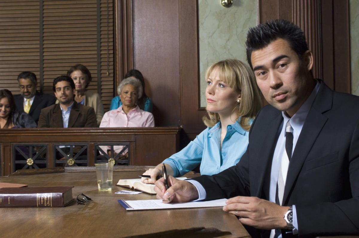 Defense Lawyer with client in court    85449032