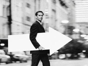 man carrying large arrow