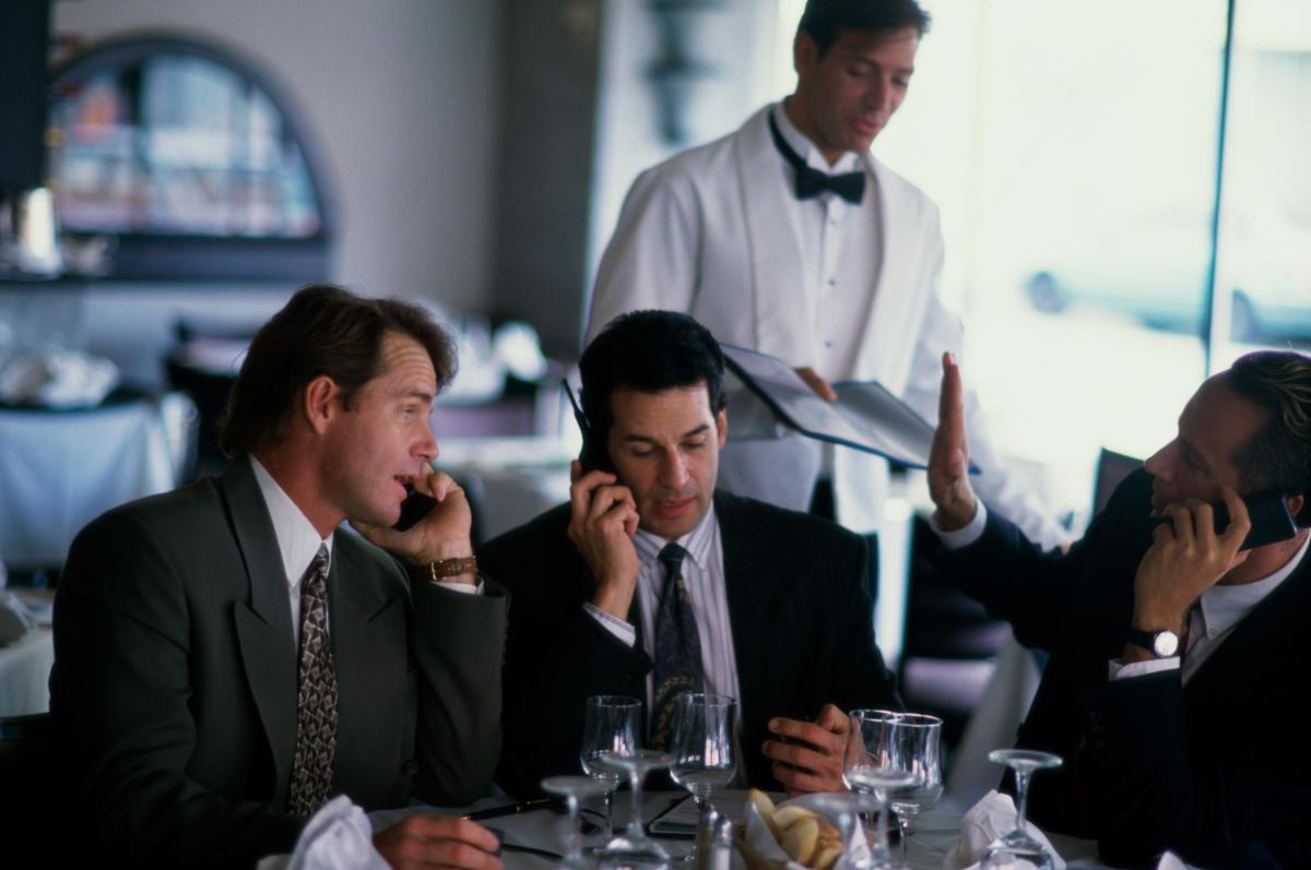 businessman on cellphones during meal 122412895