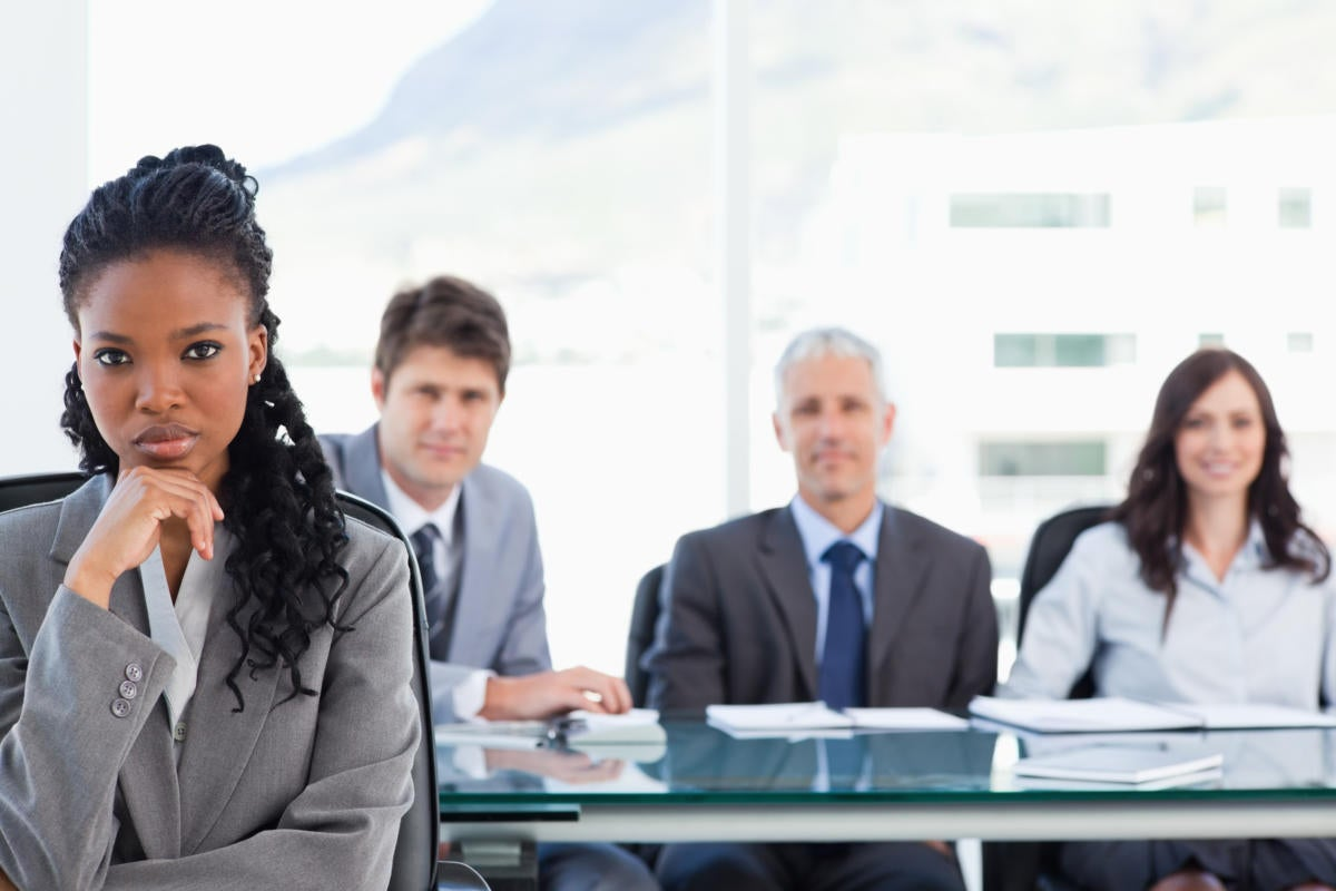 businesswoman sitting with her hand on her chin in front of her team in a meeting room151016166