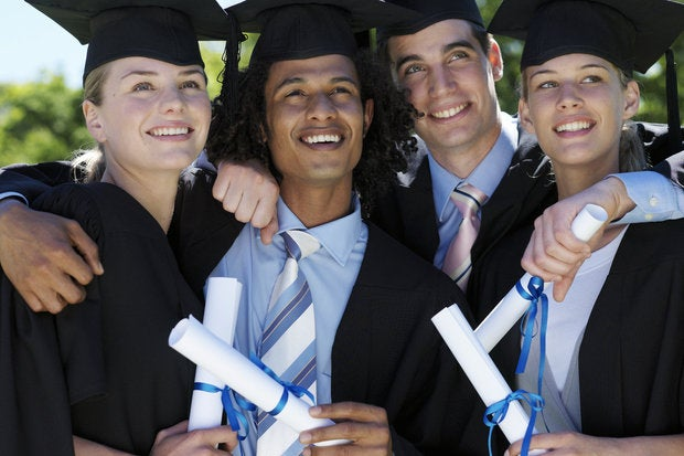 four graduate students holding diplomas outdoors 77006050