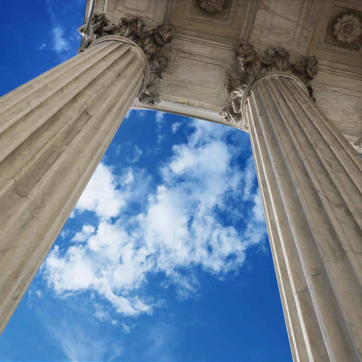 low angle view looking up at blue sky with clouds and columns of supreme court building in washingt