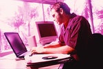 magental tinted image of worker at laptop computer 91910925