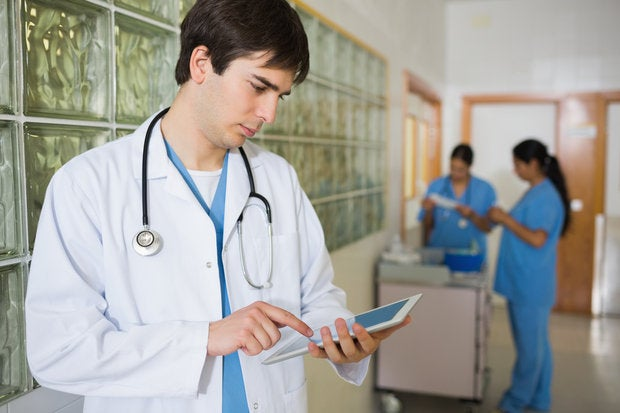 male doctor holding a tactile tablet in a hallway 151908036