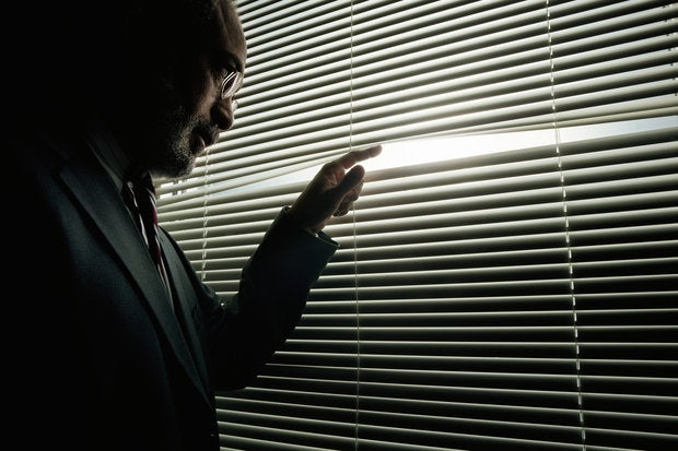 mature man peeking through window blinds 200136043 001