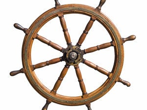 old seasoned boat steering wheel isolated on white background. usefull for leadership and skillful