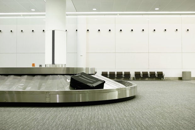 one lonely piece of luggage on an airport carousel. 93366961