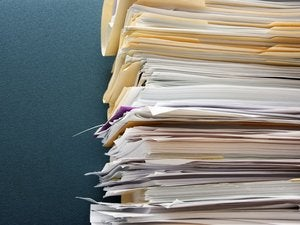 pile of paperwork against a textured green cubicle wall 92679985