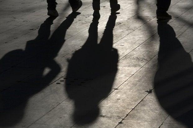 shadow over three people walking on the street 116466615