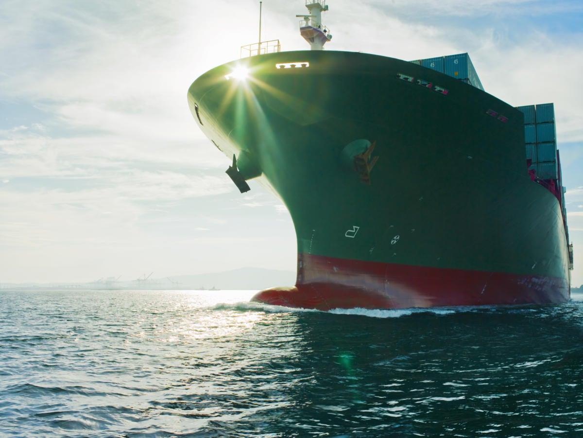 sun shining through bow of cargo ship 84039583