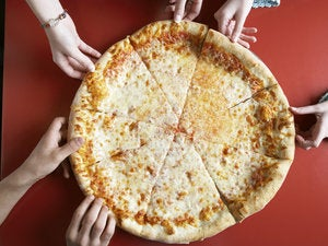 teenagers taking pizza slices at restaurant 78742347