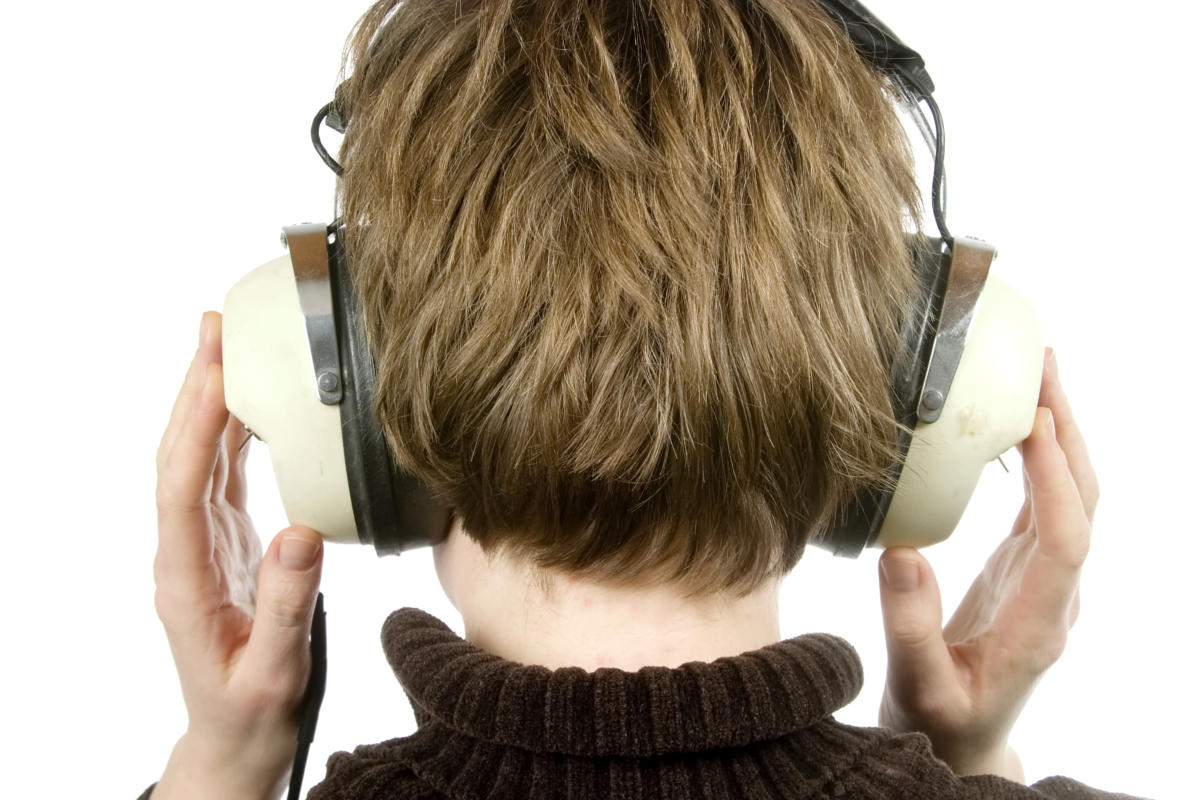the back of a person head who is listening to music with large retro earphones. their hands are up