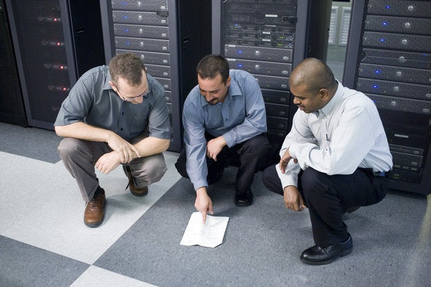 three technicians crouching in front of a network server 57569155