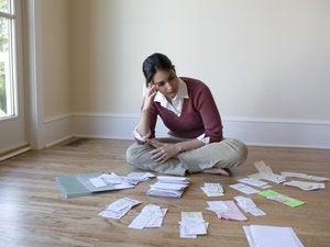 woman looking at bills and receipts on floor 83590515
