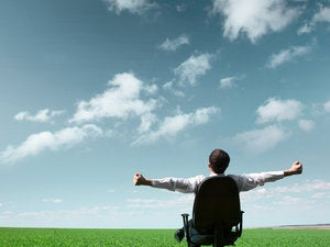Man relaxing in chair on open grassy field with blue sky