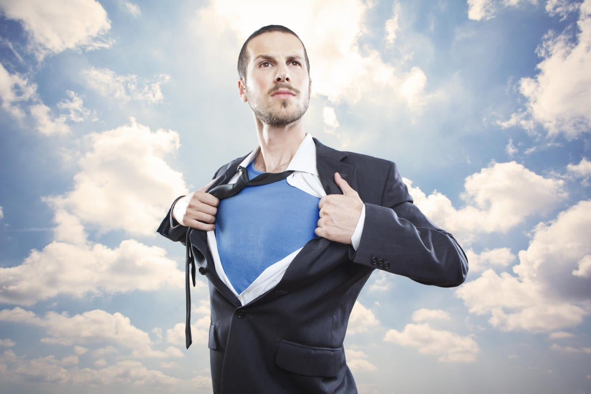 Man busting out of suit into superman among clouds