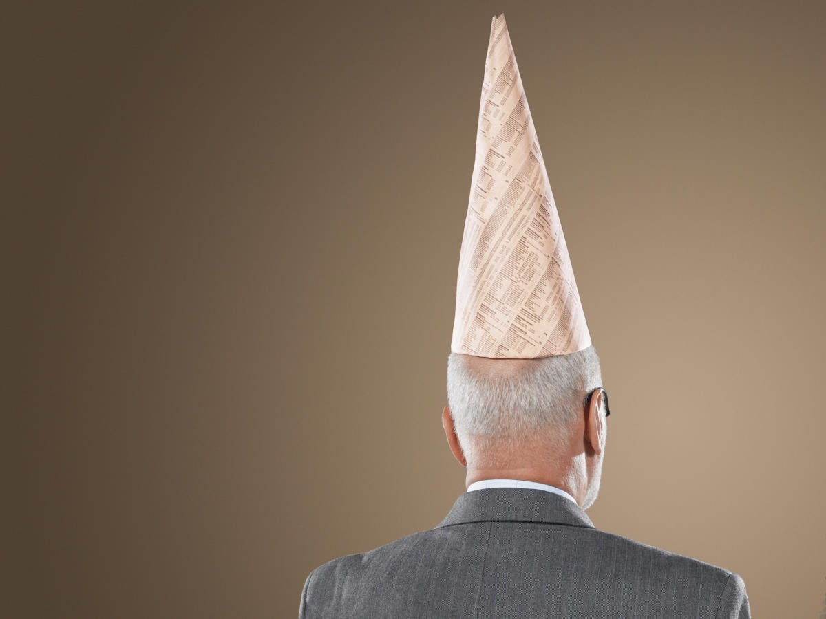Older man with dunce cap facing brown wall stupid mistake