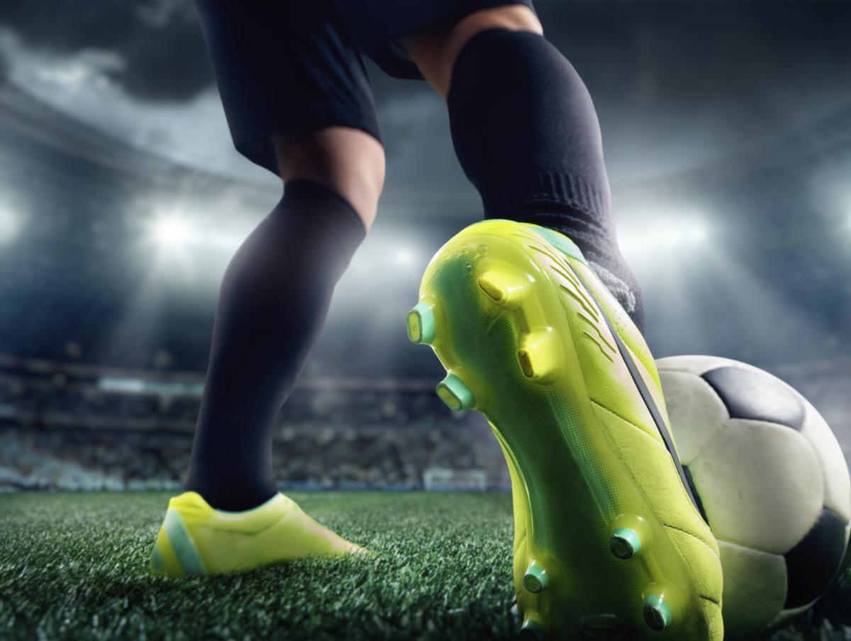 Closeup of man kicking soccer ball