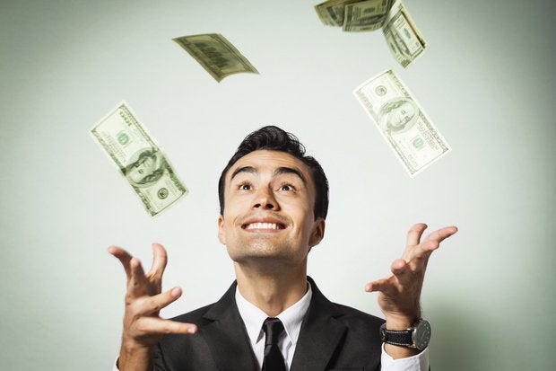 Man happily throwing money up in the air against green background