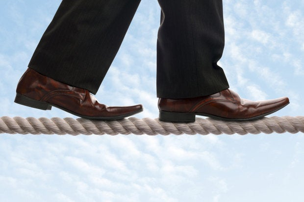 executive walking the tight rope with sky and clouds in background
