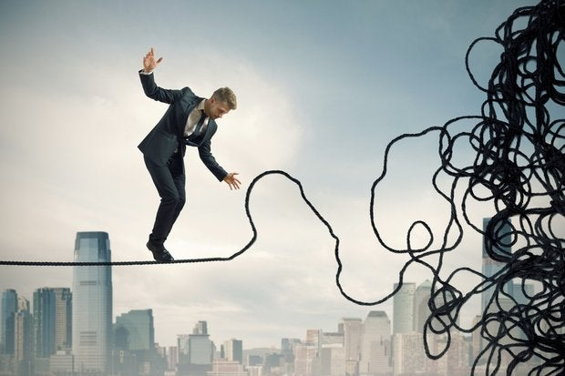 Man walking on tight rope which is unraveling problem mess danger risk