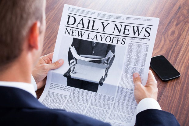 man reading newspaper layoffs jobs