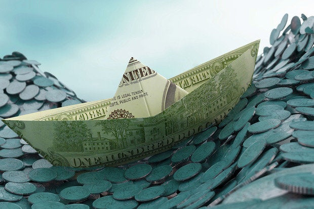 A dollar-bill ship, sailing up the crest of a wave on coin ocean.