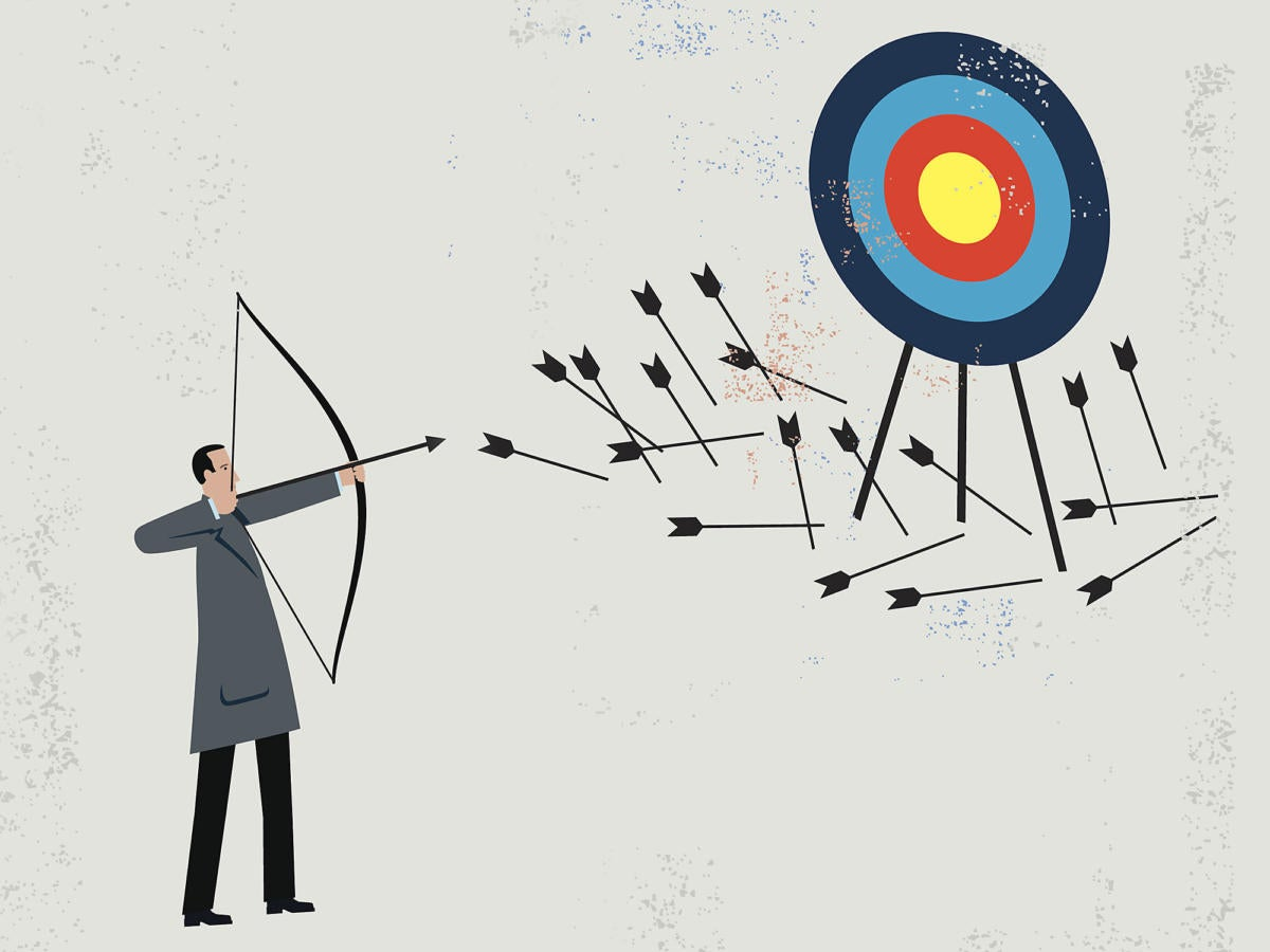 Businessman shooting arrows at a target and failing