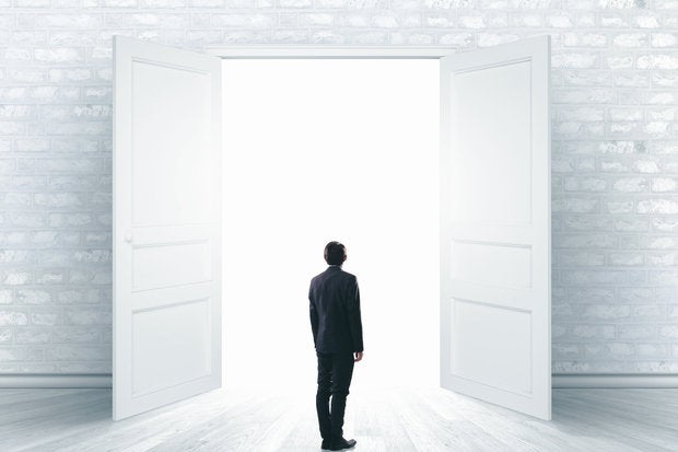young man standing in front of open doorway white background