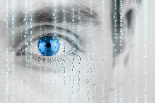 Closeup of man's blue eye with data raining down