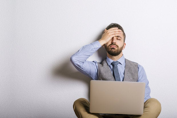 Frustrated hipster sitting with laptop