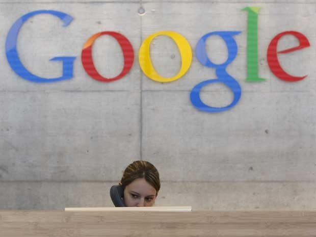 A receptionist sitting behind a desk with a Google sign behind her.
