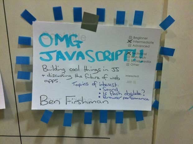 A sign that says OMG JavaScript! taped to a wall.