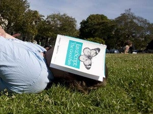 A man lying on the grass with a JavaScript book covering his face.