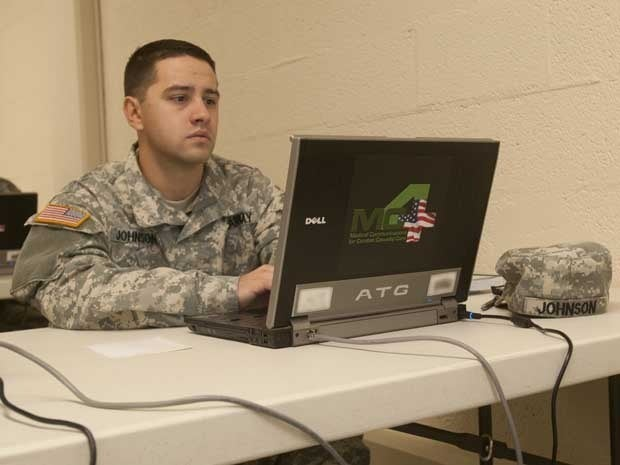 An army soldier working on a laptop