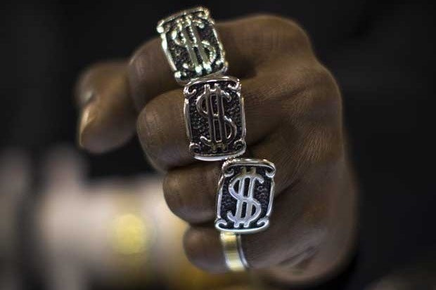 A man's hand wearing three rings with U.S. dollar signs on them