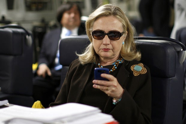 Hillary Clinton checking email on a BlackBerry