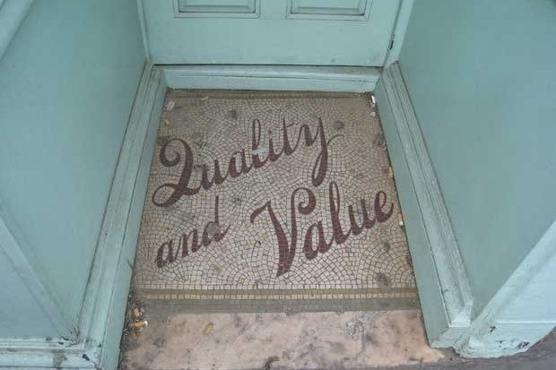 "The words ""Quality and Value"" inlaid in the floor in front of a shop entrance"