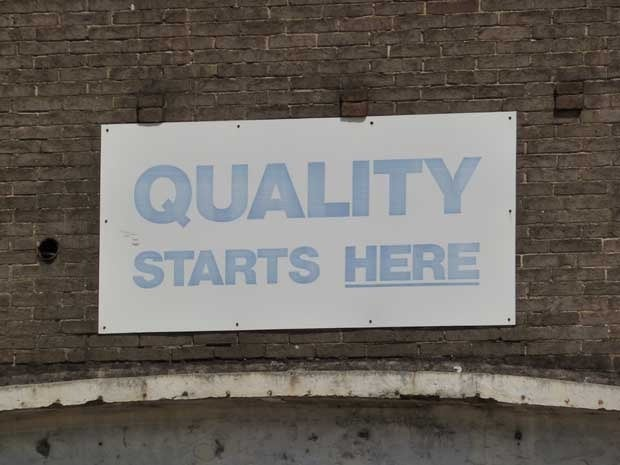 Sign on a wall that says Quality Starts Here