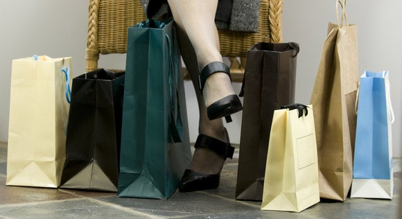 legs of woman sitting on chair surrounded by shopping bags