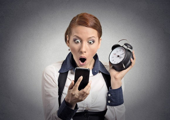 woman looking shocked holding smartphone and alarm clock