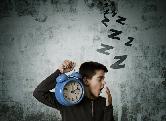 young kid holding oversized alarm clock yawning