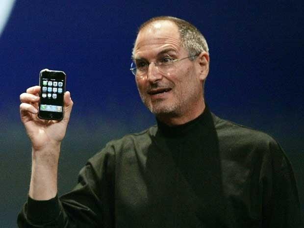 Steve Jobs holding the original iPhone