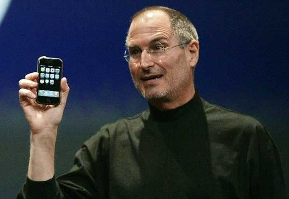 Steve Jobs holding the original iPhone