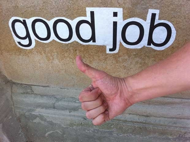 A hand giving a thumbs up in front of a sign that says Good Job
